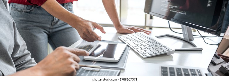 Two professional programmer cooperating and working on web site project in a software developing on desktop computer at company, codes and typing data code, Programming with HTML, PHP and javascript.