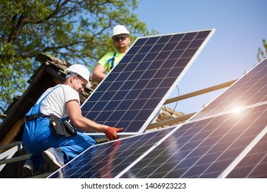 Two professional technicians adjusting heavy solar photo voltaic panels to high steel platform. Exterior solar system installation, alternative renewable green energy generation concept.