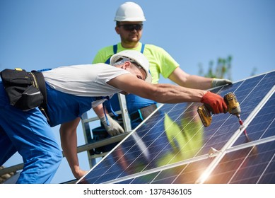 Two professional technicians installing solar photo voltaic panel to metal platform using screwdriver on bright blue sky copy space background. Stand-alone exterior solar panel system installation.