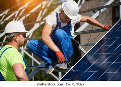 Two professional technicians installing solar photo voltaic panel to metal platform using screwdriver. Stand-alone solar panel system installation, efficiency and professionalism concept.