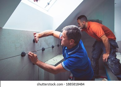 two professional tilers installing large format tiles. home renovation concept