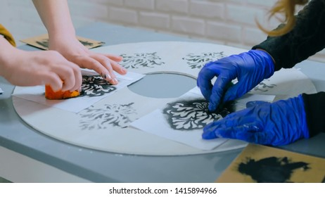 Two professional women decorators, designers painting wooden circle decoration with stencil at workshop, studio - close up shot. Paint, handmade and art concept