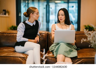 Two professional women have a business discussion on a couch in an office. One is a Caucasian woman and the other is an Asian Chinese woman with a laptop computer.