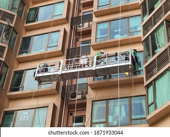 Two Professional workers use a suspended cradle or steeplejack to access and clean windows of typical high rise building or skyscraper in Hong Kong before Christmas or New Year