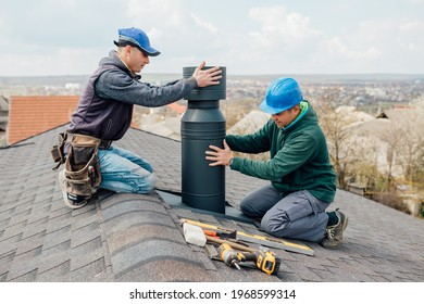 two Professional workmen's standing roof top and measuring chimney of new house under construction against blue background
