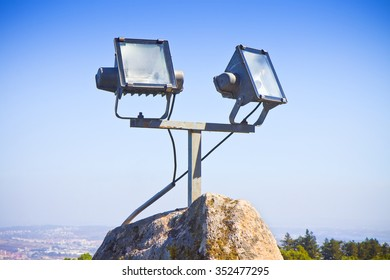 Two projectors of light against a sky background