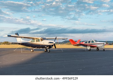 Two prop planes on the tarmac at sunrise