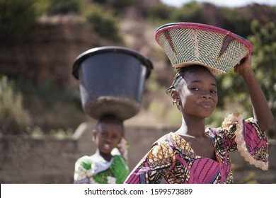Two Proud African Girls Carrying Heavy Household Items On Their Head