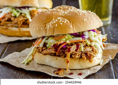 Two pulled pork barbeque sandwiches with coleslaw sitting on wooden table with glass of beer