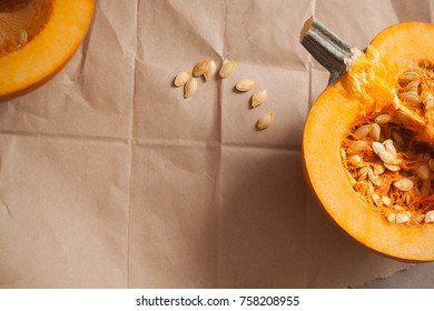 Two pumpkin halves on a brown paper background with pumpkin seeds and copy space for Thanksgiving and fall themes.