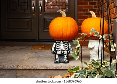 Two pumpkin-heads on small skeleton Halloween cute sculpture standing at the front doors outside of the fancy home. Season outdoor decoration