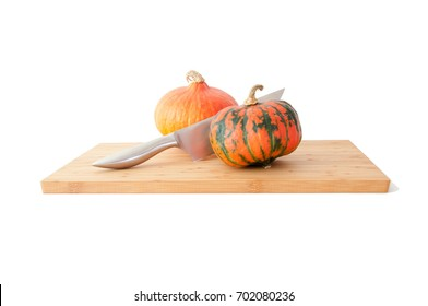 Two pumpkins on a bamboo board with knife