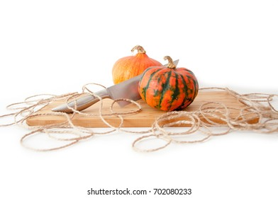 Two pumpkins on a bamboo plate with one blade and string