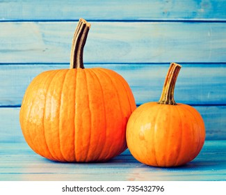 Two pumpkins over turquoise colored wood