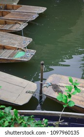 Two punts secured to a metal pole sunk in the river Cherwell, in Oxford, five punts in background to left side of photo. Chain lying on hull of boat with leaves in foreground.