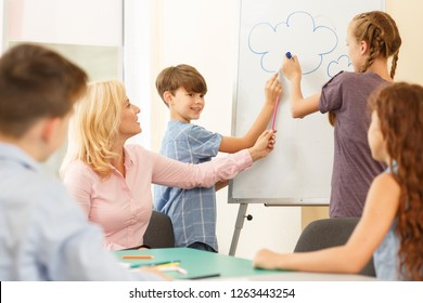 Two pupil standing on white board and drawing clouds using marker with teacher tips in light class. Girl pointing to picture, and her classmates sitting at table, listen carefully and looking at her.