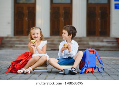 Two pupils of primary school. Boy and girl with school bags behind the back. Beginning of school lessons. Warm day of fall. Back to school. Little first graders.