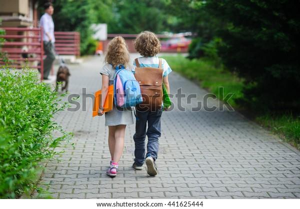 Zwei Schüler der Grundschule gehen Hand in Hand. Junge und Mädchen mit Schultaschen hinter dem Rücken. Beginn des Schulunterrichts. Warmer Herbsttag. Zurück zur Schule.  Kleine erste Grader.