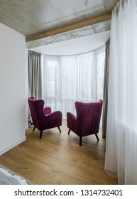 Two purple chairs by the window in the bay window. Interior of a modern apartment.