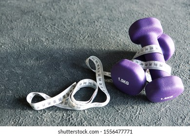 Two purple fitness dumbbells and centimeter  on grey textured background. Healthy life, sport and diet concept.  Top view, flat lay. Selective focus.