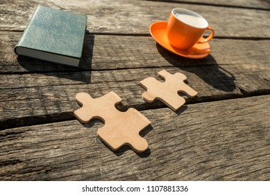 Two puzzle pieces, green note pad and cup of coffee lying on a textured wooden desk. Conceptual of education and problem solving.
