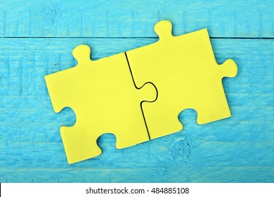 Two puzzle pieces on wooden table