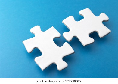 Two puzzle pieces.Close-up of puzzle pieces on blue background.