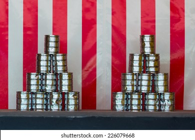 Two pyramids of tin cans for throwing balls at them on red white striped background