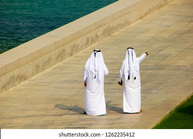 Two Qatari business men wearing white thob are meeting outside on a public place and one is pointing to a certain direction. Typical Arab fashion