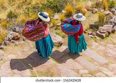 Two Quechua indigenous women in traditional clothing and textile walking down the steps on Taquile island by the Titicaca Lake, Puno, Peru.