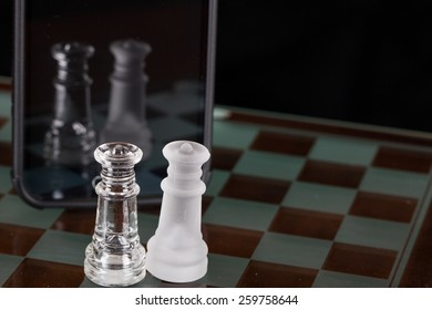Two queens from a glass chess set on the glass board with a smart phone in front of them.  They can see their reflection in the phones screen.