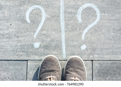 Two question marks are handwritten on an asphalt road with sneakers