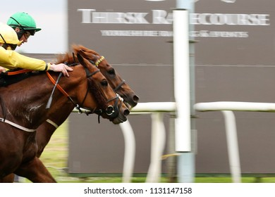 Two racehorses enter the frame in a photo finish before the Winning Post at Thirsk Races - camera pan with blur : Thirsk Racecourse, Thirsk, North Yorkshire, UK : 19 June 2018 :