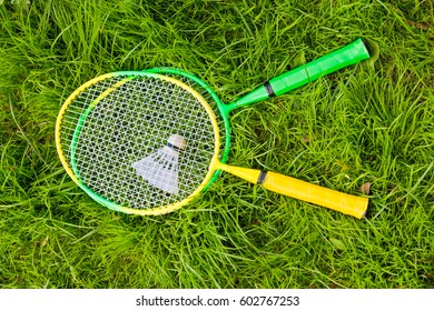 two rackets for badminton and a shuttlecock on the grass