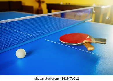 Two rackets for a table tennis or Ping-Pong and a ball on a blue table.