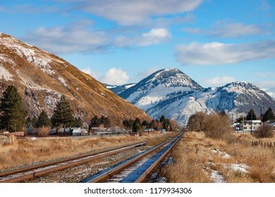Two railway tracks lead through scrub to distant snowy mountains