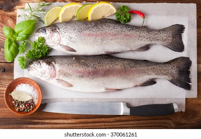 Two rainbow trout on a board, with herbs and peppercorns, ready for cooking.