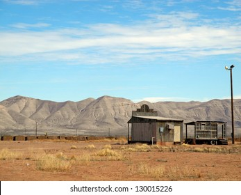 Two ramshackle vintage buildings open onto a great expanse of blue sky and mountain ridges, in Texas.