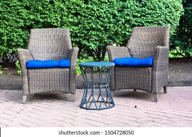 two ratan chairs  with blue cushions outside with a small decorative table on brick with green bush background