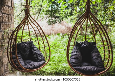 Two rattan hanging wicker chairs with black pillows in garden, summertime