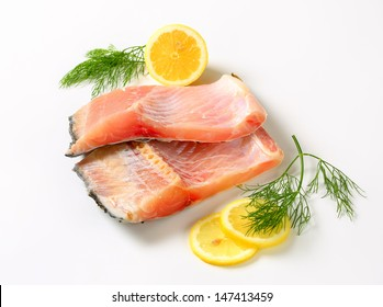 two raw carp fillets with slices of lemon and dill