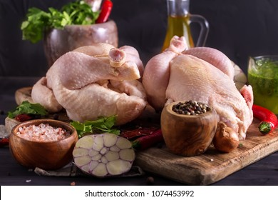 Two raw chickens on rustic wooden board with herbs and spices