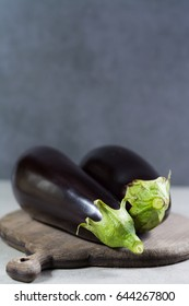 Two raw eggplants or aubergins vegetables, ready to cook on wooden background