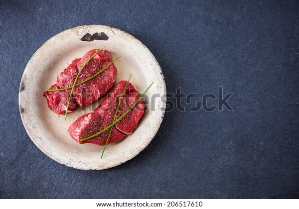 Two raw fillet steaks on an old plate with a slate background