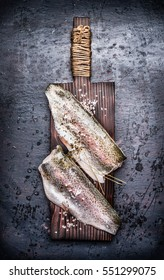 Two Raw fish fillet on old wooden cutting board on dark rustic background, top view