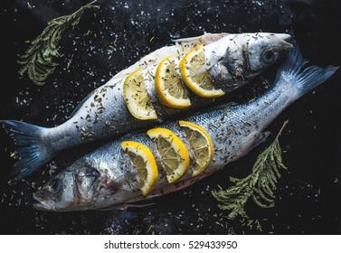Two raw fish with lemon on black cutting board. Sea bass fish