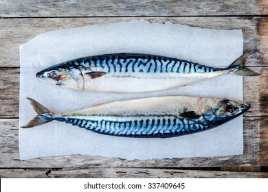 Two raw fresh mackerel fishes on a paper on wooden table