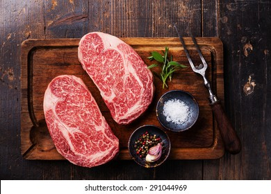 Two Raw fresh marbled meat Black Angus Steak Ribeye, seasonings and meat fork on dark wooden background