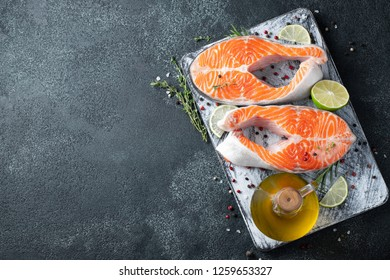 Two raw fresh salmon or trout steaks, rich in omega-3 oil, with lime, thyme and olive oil on a dark background. Healthy and dietary food. Top view with copy space. Flat lay
