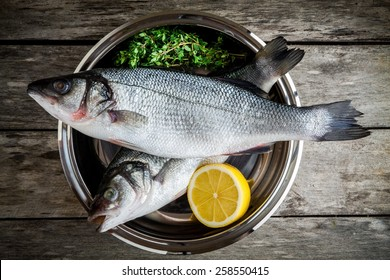 two raw fresh sea bass in a bowl with thyme and lemon on wooden table